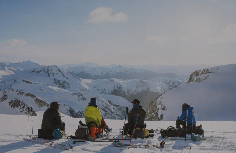 Skiers sitting on a mountain enjoying the view